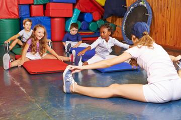 Kinder turnen mit Sportlehrer in Grundschule
