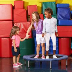 Kinder springen auf Trampolin in Turnhalle