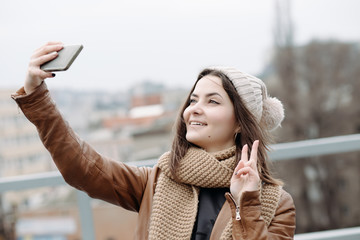 Positive young girl make a selfie at city background