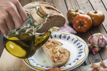 Chef que se dispone a verter aceite de oliva sobre una tostada de pan con tomate, ajo y jamón.