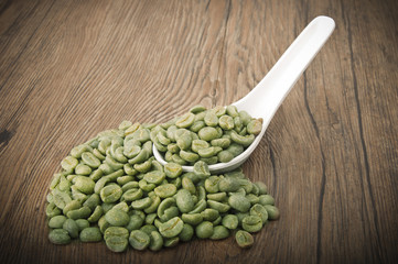Wall Mural - Spoon with green coffee beans on the wood