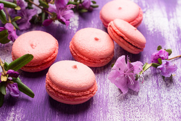 Bright macaroons on the wooden background. Shallow depth of field.