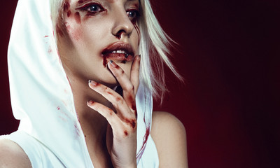 gothic strange girl blonde vampire blood halloween. in the studio on a red background. beauty shot