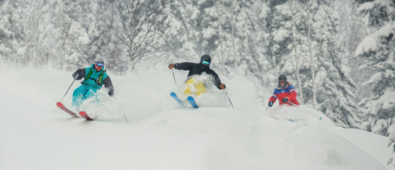 Three skiing friends moving downhill