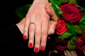 Closeup shot of holding female with engagement ring and male hands with red roses bouquet on background indoors