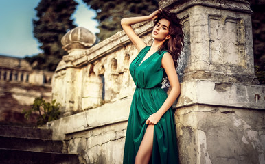 beautiful sexy brunette girl with long hair, make-up in a green dress on a background of the beautiful architecture