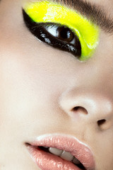 Close-up portrait of girl with yellow and black make-up creative art. Beauty face.