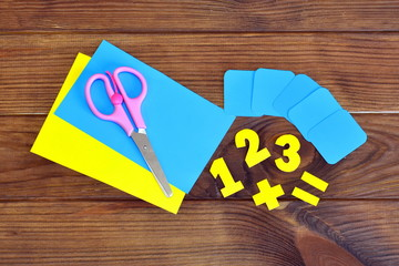 Paper sheets and numbers, scissors on a brown wooden background
