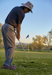 Man golfer chipping to putting green late afternoon golf round