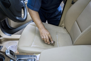 Hand cleaning the leather car seat