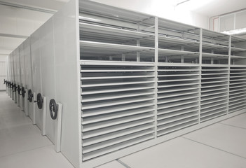 Art history museum depository warehouse archive with empty grey shelves and storage space.