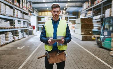 Obraz Young handyman or builder in a warehouse - fototapety do salonu
