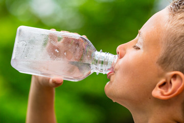 Boy drinking clean tap water from transparent plastic bottle
