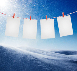 Blank paper or photo frames hanging on the red striped rope. Snowstorm in sunny day background