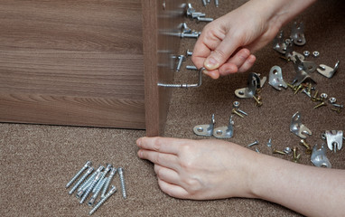 Furniture wooden assembly frame manually tightening screw using hex wrench.