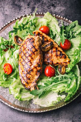 Grilled chicken breast in different variations with lettuce salad cherry tomatoes .mushrooms herbs cut lemon on a wooden board or teflon pan. Traditional cuisine. Grill kitchen.