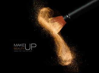 Cosmetics brush with glowing face powder. Dust explosion