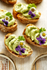 Sandwiches with avocado paste with the addition of edible flowers violets and daisies