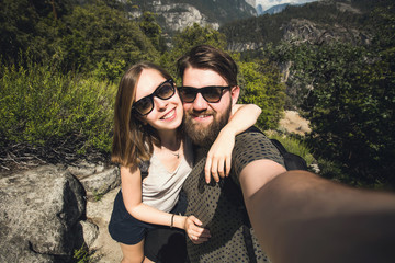 Happy young couple take selfie while hiking in Yosemite National Park, California, USA