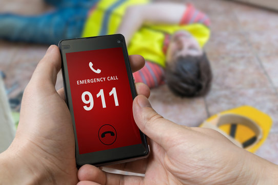 Man dialing emergency (911 number) on smartphone. Injured worker had accident and is lying on the floor.