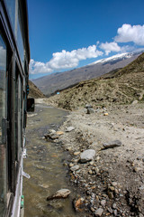 A bus on a very bad road, with water flowing, on the popular highway, for tourism, between Manali, Himachal Pradesh to Leh, Ladhak, Jammu & Kashmir in India