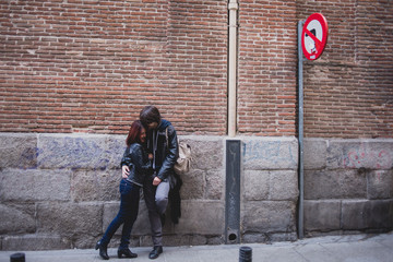 Couple leaning against a wall in the street
