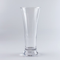 Empty beer glass against white background