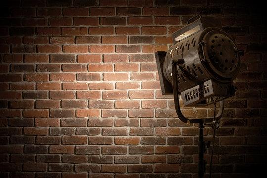 vintage theatre/movie spot light focused on a brick wall background