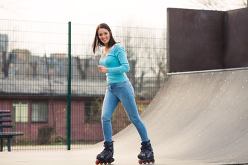 Smiling young girl with rollerblades exercising on a ramp in a skate park