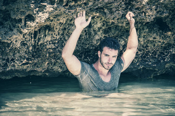 Athletic man in the sea or ocean by rocks, wet t-shirt