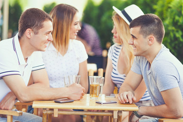 Group of young friends having fun sitting in a cafe chatting and smiling while having a drink