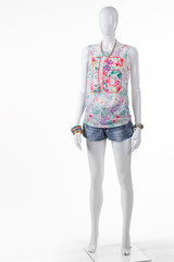 Woman's short blue denim shorts. Summer denim shorts on mannequin. Colorful top with denim shorts. Summer collection in outlet store.