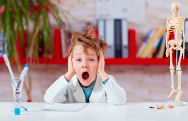 young kid, schoolboy yawning during experiment in school lab