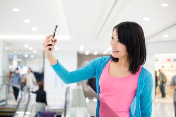 Woman take self photo inside shopping mall
