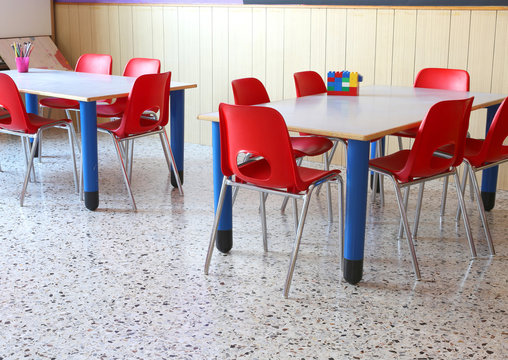 classroom of a kindergarten with red chairs and small school tab