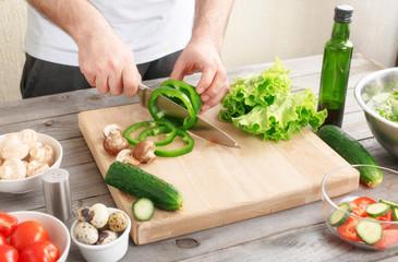 man prepares a salad of fresh vegetables