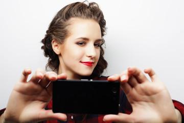 Pretty hipster girl taking selfie.