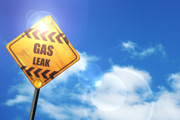 Yellow road sign with a blue sky and white clouds: Gas leak back
