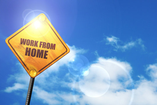 Yellow road sign with a blue sky and white clouds: work from hom