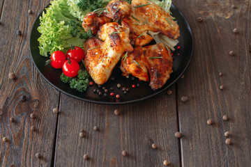 Wall Mural - Grilled spicy chicken wings with lettuce and tomatoes cherry. Baked chicken with fresh vegetables. Top view of homemade meat on wooden table.