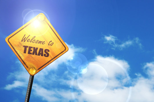 Yellow road sign with a blue sky and white clouds: Welcome to te