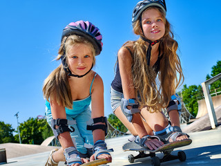 Two Children in helmet skateboarding on his skateboard outdoor. lower plan. Very happy.