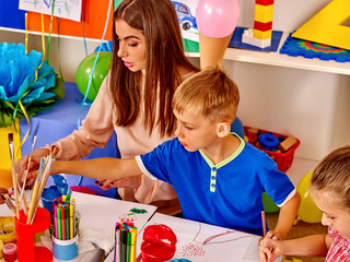 Happy children and teacher draw paints in the kids' club.