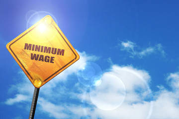 Yellow road sign with a blue sky and white clouds: minimum wage