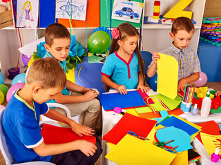 Group kids holding colored paper on table in kindergarten. Children learn to cut out shapes in kindergarten.