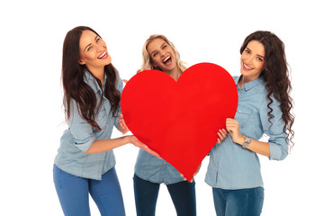 three laughing casual women holding a big red heart
