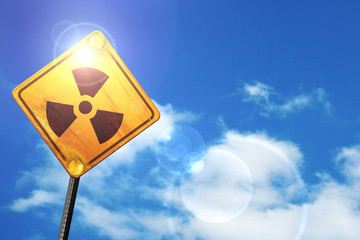 Yellow road sign with a blue sky and white clouds: Nuclear dange
