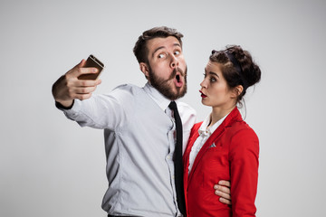 Two colleagues friends taking selfie with telephone camera