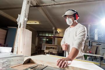 Carpenter working on wood machine in factory