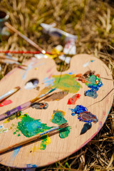 Used brushes near picture with an artist's palette of colorful oil paint for drawing and painting lying on the grass, closeup
